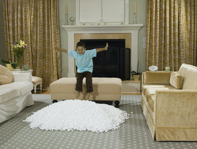 Boy (3-4) jumping into pile of Styrofoam packing peanuts on living room floor
