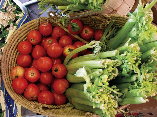 A basket of tomatoes and celery stalks