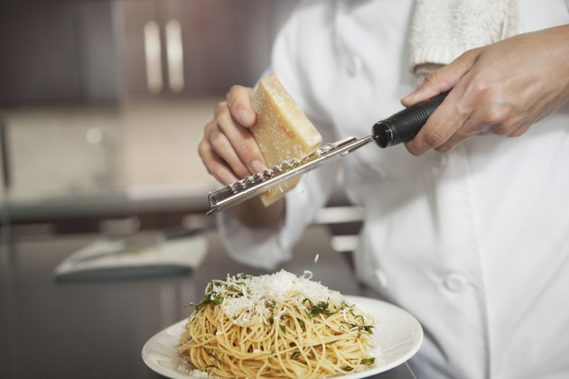 Chef Grating Cheese Onto Pasta In Kitchen