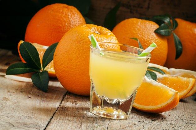 Orange juice in a glass with striped straws