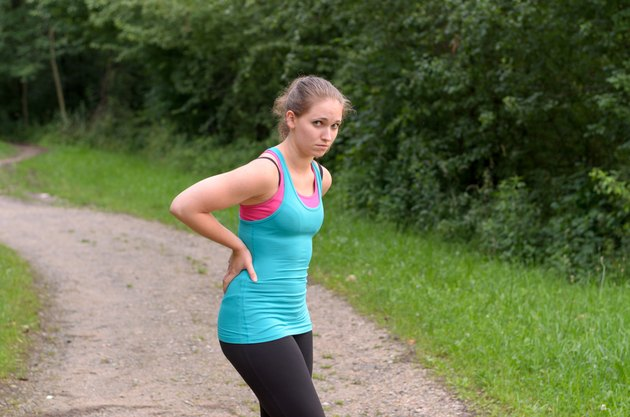 Athletic Woman Having a Back Pain While Exercising