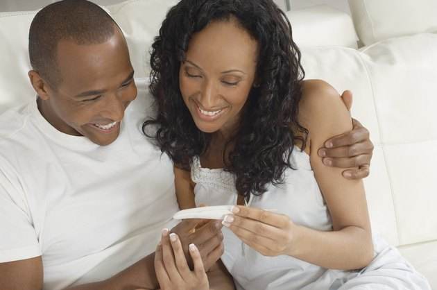 Couple examining pregnancy test in bed