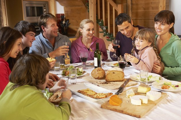 Two Families Enjoying Meal In Alpine Chalet Together