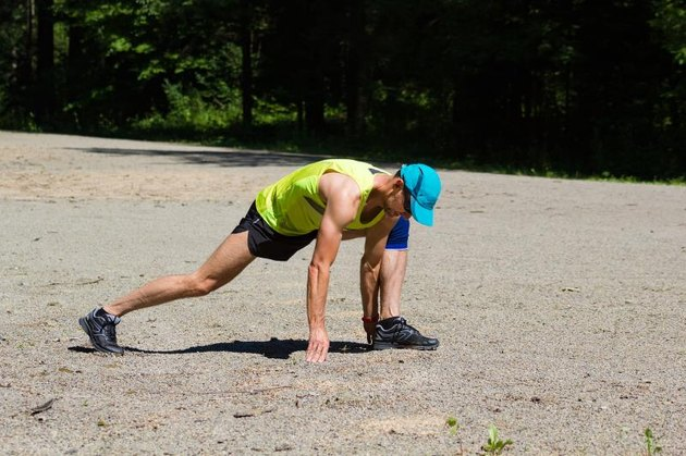 Athlete male runner stretching outdoors. Lizard lunge. Forward lunge elbow to instep.