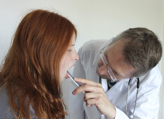 Image of hospital doctor looking at girl patient's sore throat
