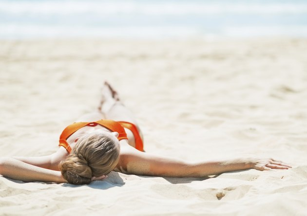 young woman laying on beach. rear view