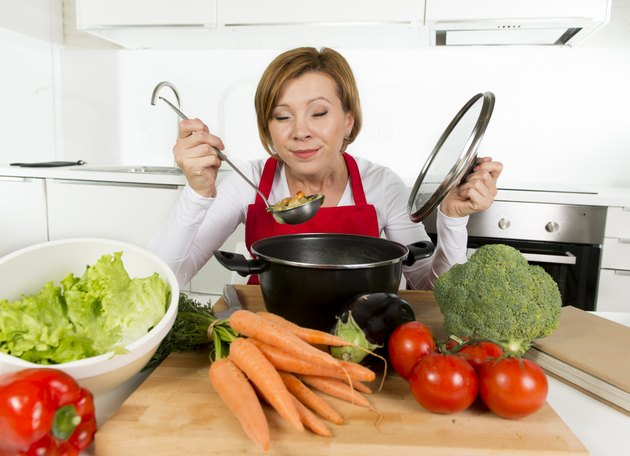 home cook woman at kitchen holding saucepan tasting hot soup