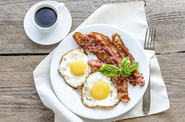 Fried eggs with bacon on the wooden table