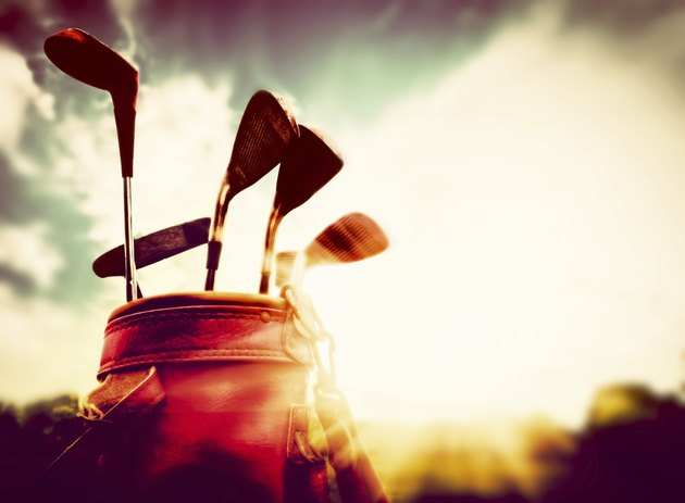 Golf clubs in a leather baggage vintage style at sunset
