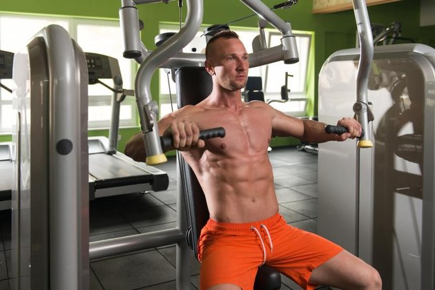 Young Bodybuilder Doing Heavy Weight Exercise For Chest On Machine