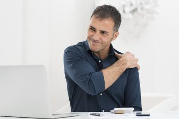 Portrait Of Mature Man At Work Suffering From Shoulder Pain