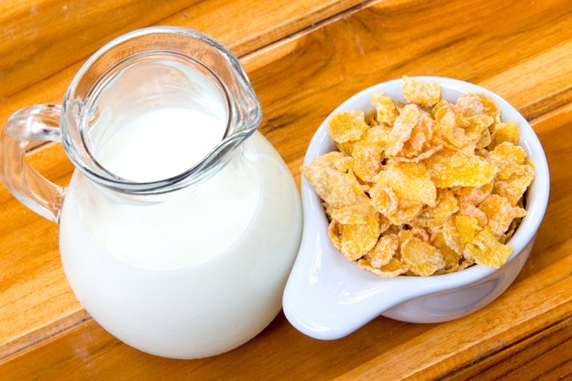 Corn flakes in white bowl and milk on wooden table