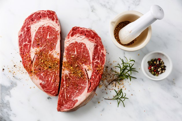 Heart shape Raw meat Ribeye Steak with pepper and rosemary