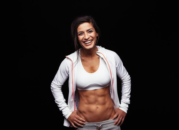 Happy young woman in sports clothing standing with hands on hips smiling. Muscular fitness model on black background.