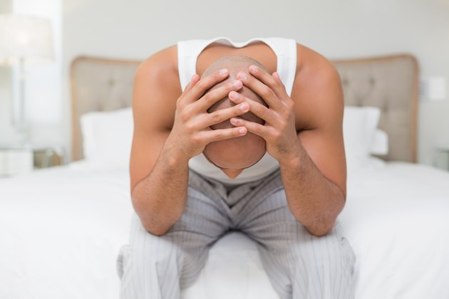 Thoughtful bald man with head in hands on bed