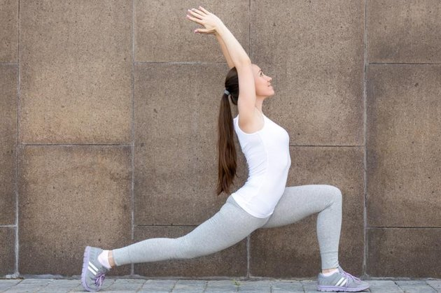 Sporty attractive girl practicing yoga, standing in Horse rider exercise, anjaneyasana pose, working out, wearing sportswear, outdoor full length, urban street background, against the wall