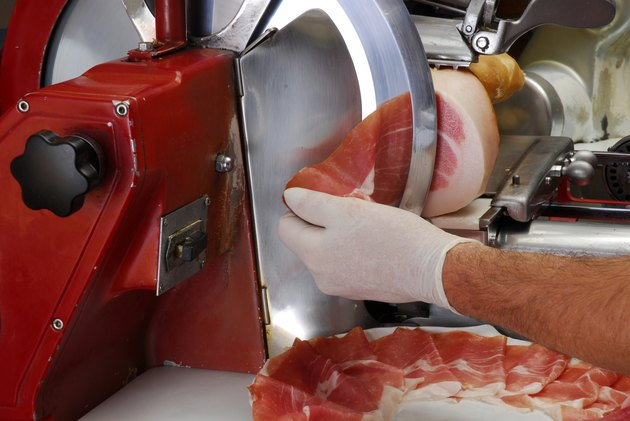 worker slicing ham using machine
