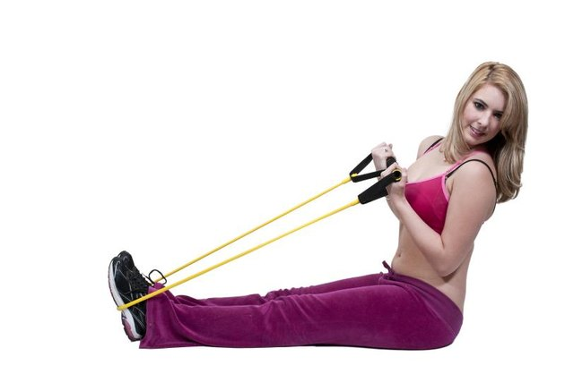 Beautiful young woman working out with resistance band tubes