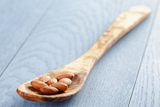 roasted almonds in spoon on blue wooden table