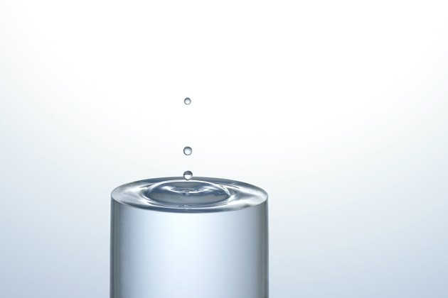 Water dropping onto a full glass of water, creating concentric circles on the surface