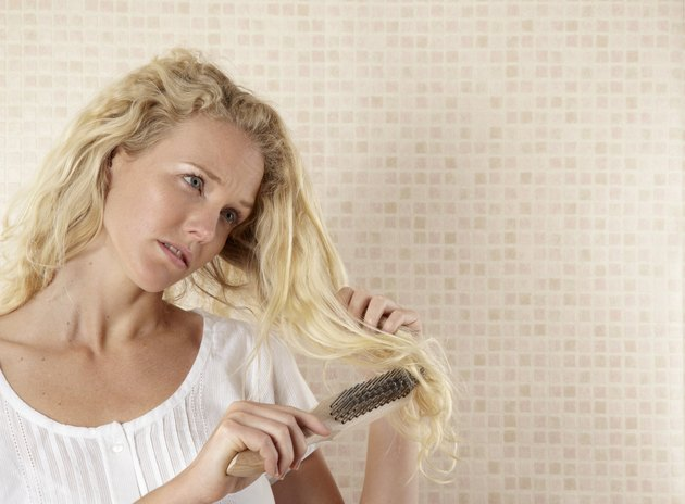 Young woman brushing hair with DIY metal brush