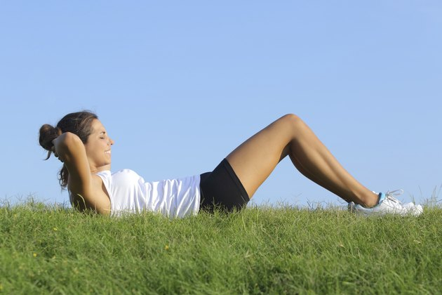 Beautiful woman doing crunches on the grass