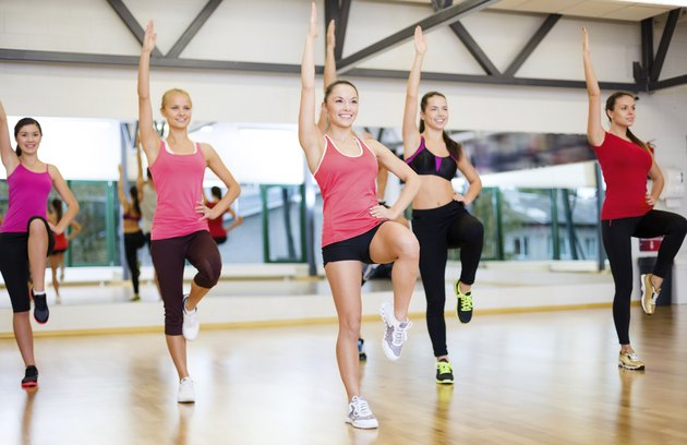 group of smiling women exercising in the gym