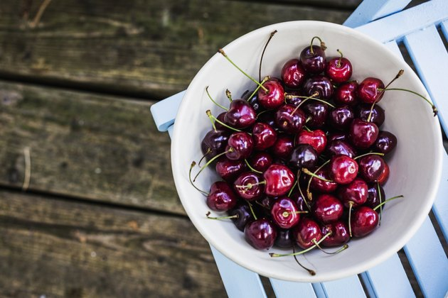 Bowl of cherries on top of patio chair