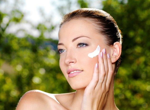 Beautiful woman applying cream on cheek