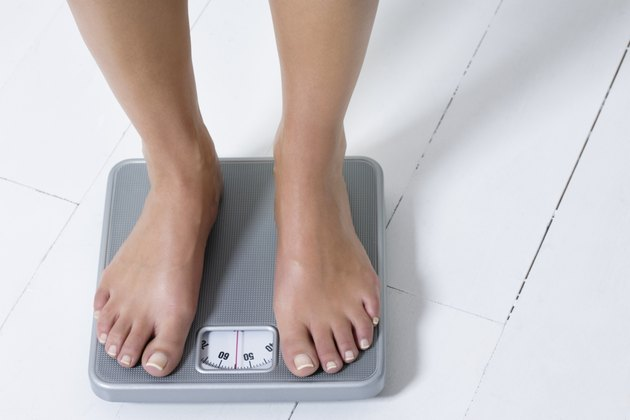 Young woman weighing herself