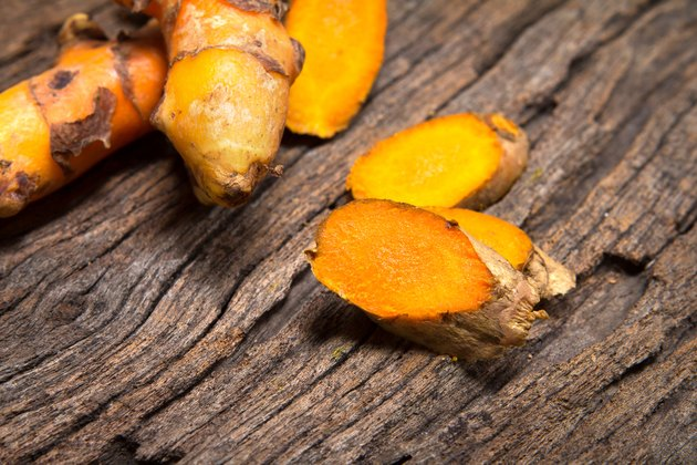 turmeric root on wooden plate
