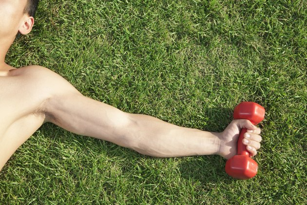 Close Up on Arm and Shoulder Holding Dumbbell in Grass