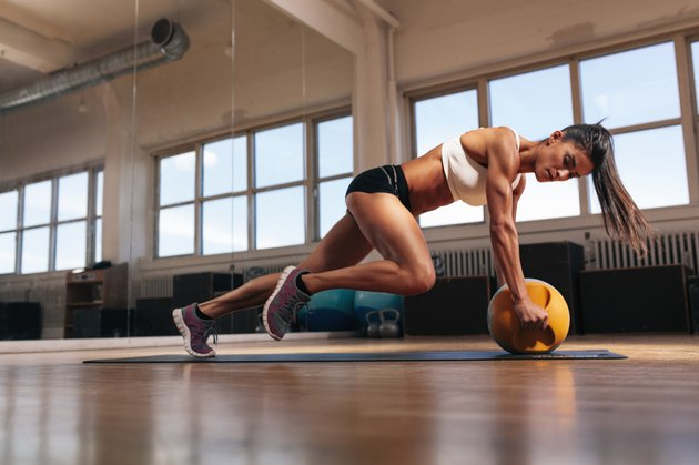 Muscular woman doing intense core workout