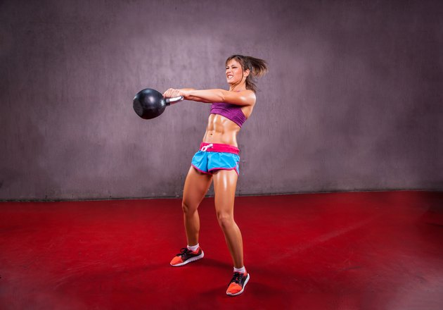 Young Woman Lifting  Kettle Bell