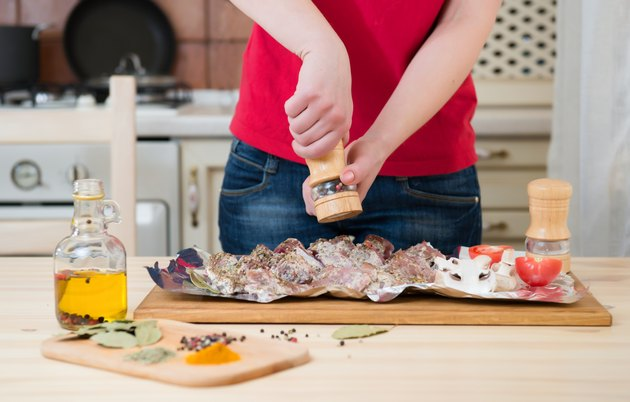 Woman hands cooking at home kitchen. Girl peppers meat.