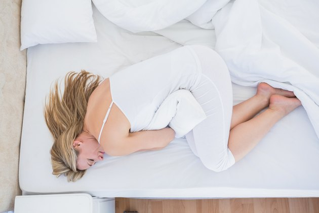 Blonde woman lying in bed getting stomach pain