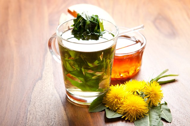 herbal dandelion tea with fresh leaf inside teacup