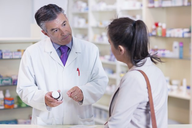 Pharmacist holding a bottle of drugs talking to customer