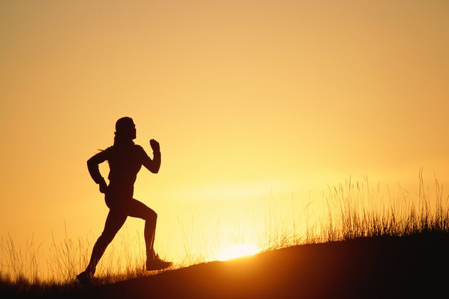 Silhouette of person running up hill