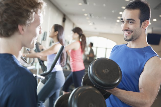 Portrait of young muscular man lifting weights in the gym