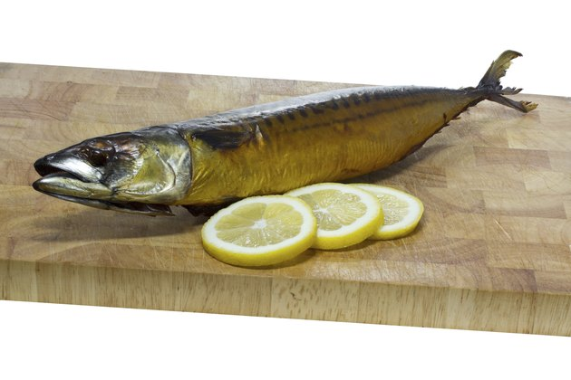 Smoked mackerel on a wooden board with lemmon