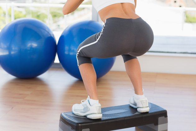 Low section rear view of a fit woman exercising on step
