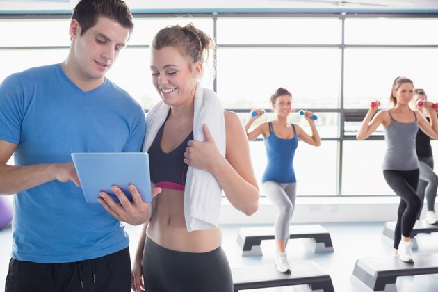 Trainer and woman talking while aerobics class lifiting weights
