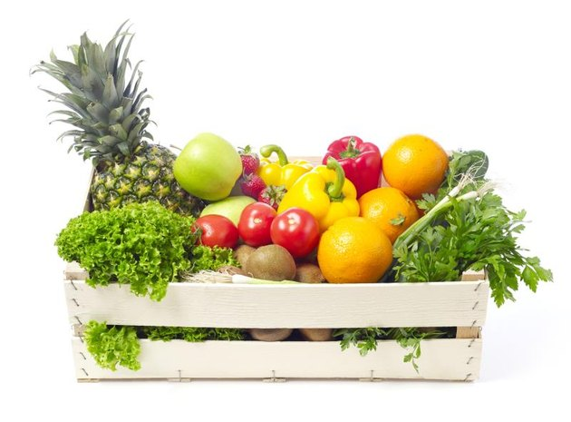 Fruits and vegetables in a wooden crate isolated on white