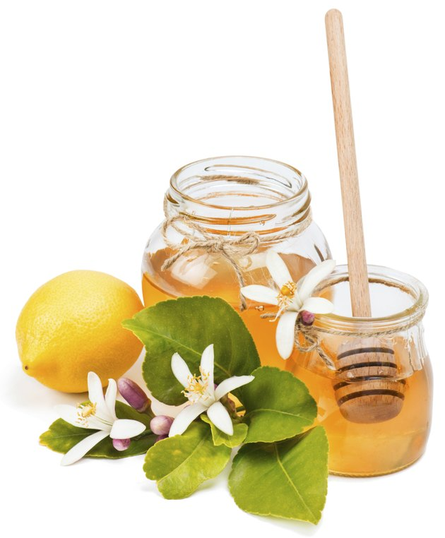Glass jars of lemon honey with flowers