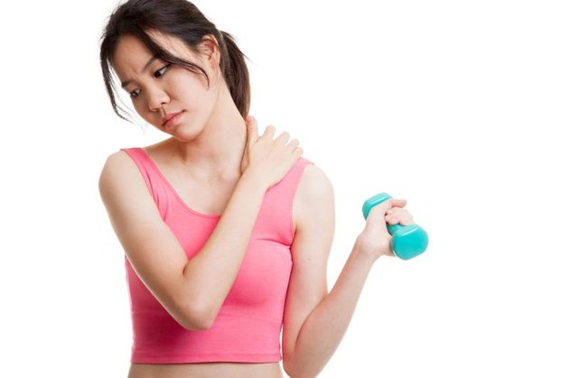 Asian healthy girl got shoulder pain with dumbbell  isolated on white background.