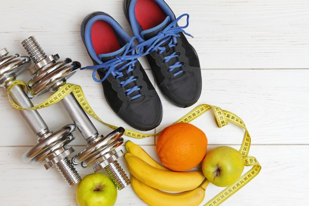 fitness equipment and healthy nutrition on white wooden floor