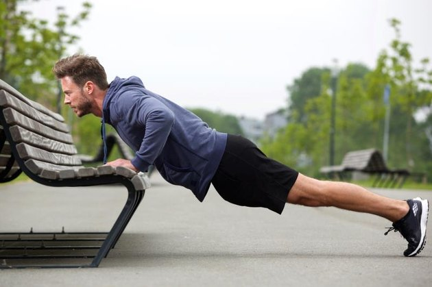 Full length side portrait of attractive man doing pushup outside