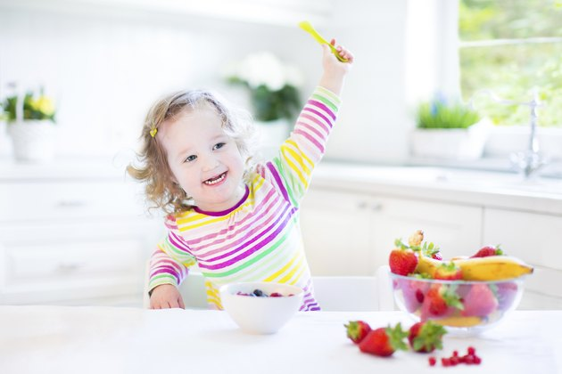 Toddler girl with curly hair wearing colorful shirt having breakfast