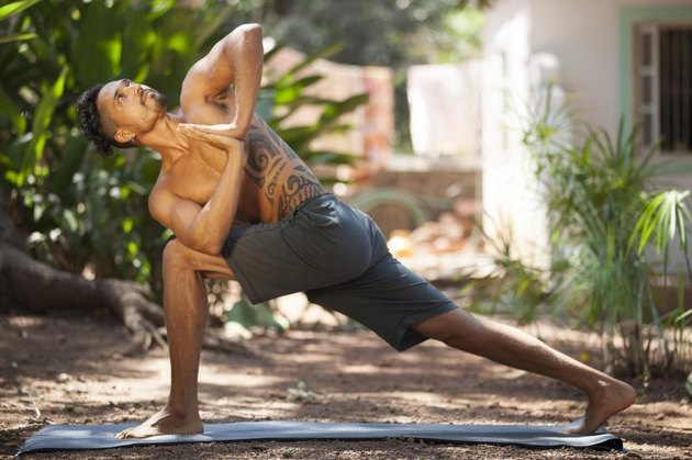 Young man does yoga in nature.